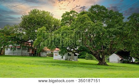 Sunset Over An Historic Homestead Set In Parkland Amongst Lush Green Grass