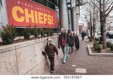 Kansas City, Missouri - February 5, 2020: A Family Walking On The Sidewalk Next To A Chiefs Banner I