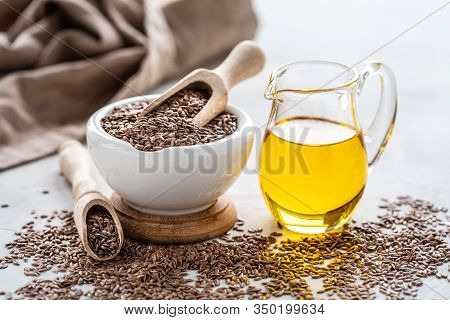 Flaxseed Oil In A Bottle And Ceramic Bowl With Brown Flax Seeds And Wooden Spoon On A White Backgrou