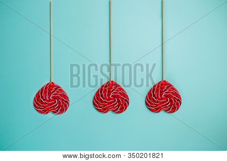 Heart Shaped Red Lollipop On Blue Background. Colorful Lollipop Patterns. Red And White Lollipop Wit