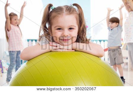 Sporty Kid With Children Group Having Fun In Gym