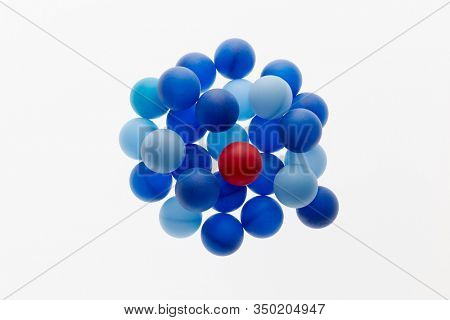 Red ball among blue spheres. Singularity concept.