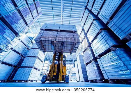 Forklift Loader In Storage Warehouse Ship Yard. Distribution Products.