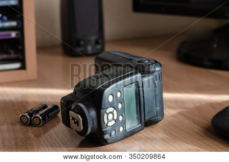 An External Flash For The Digital Camera Lies On Its Side On The Table. Closeup Of A Black Used Came
