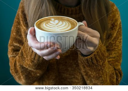 Woman In Terracotta Sweater Headless And Hands With Latte. Turquoise Background.