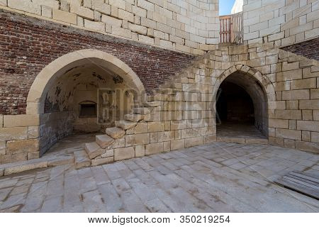 Exterior Of Ancient Brick Building With Shabby Stone Stairway And Two Crumbling Arched Alcoves On St