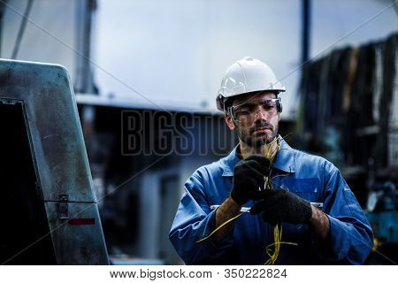 Staff Engineer Male Employee At A Factory Plant Operating A Production Line Machine And Setting It F