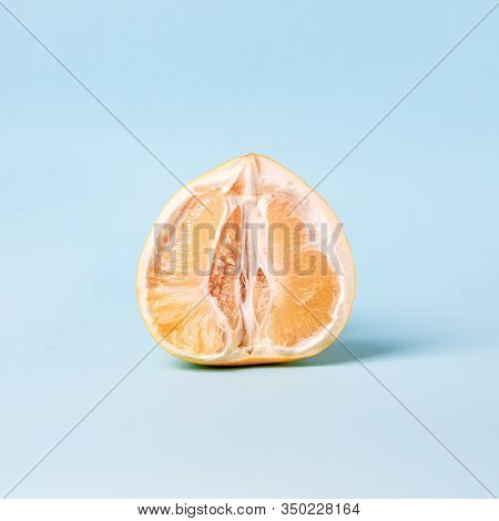 Half Of Fresh Pomelo Citrus On Color Blue Background. Erotic Concept, Vagina Idea, Woman Intimate He