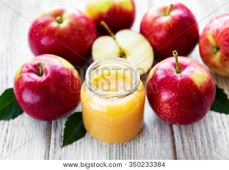 Applesauce In Glass Jar And Fresh Apples On A Wooden Table