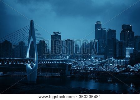 CHONGQING, CHINA – MARCH 13: Qiansimen Bridge and Hongyadong complex at night on March 13, 2018 in Chongqing. With 17M population, it is the most populous Chinese municipality.
