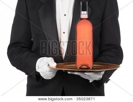 Butler wearing a tuxedo holding bottle of red wine on a serving tray. Horizontal format showing persons torso only.
