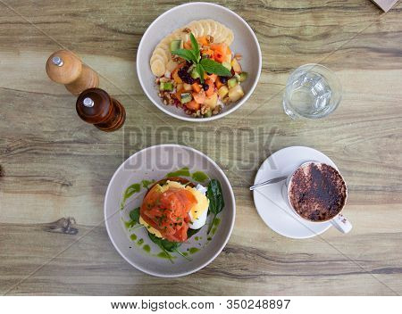 Delicious Breakfast Plates Of Smoked Salmon Poached Eggs On Toast And Fresh Fruit Salad With Yoghurt