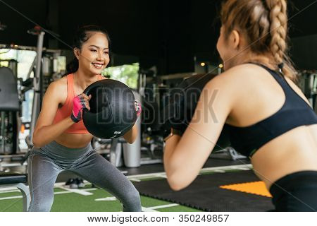 Happy Young Female Athletic People Performing Squat Exercises With Friend And Holding A Medicine Bal