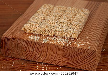 Honey Bars With Sesame Seeds Close-up On Wooden Background. Gozinaki Sweets. Traditional Oriental Co
