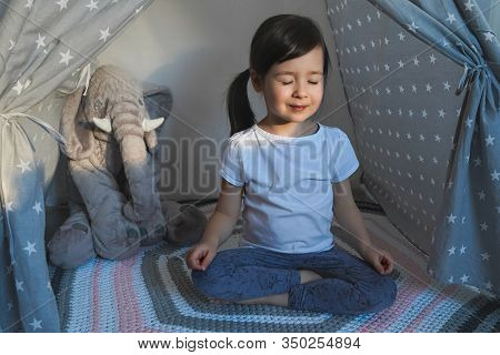 The Child Does Yoga. Little Girl Is Sitting In Lotus Position. Childrens Yoga For Spinal Health.