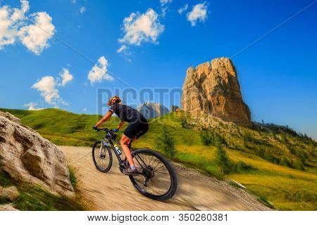 Motion blur picture of woman cycling in Cortina d'Ampezzo, stunning rocky mountains on the background. Woman riding MTB enduro flow trail. South Tyrol province of Italy, Dolomites.