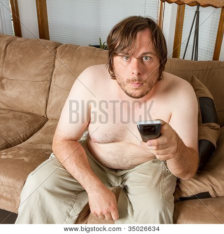 Young Man Sitting On The Couch Working The Tv