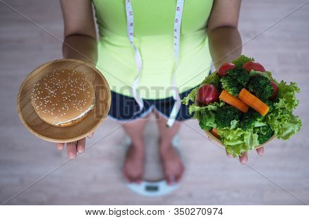 Woman Weighing And Holding Vegetable Dish With Hamburger. Food Concept