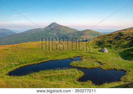 A Mountain Lake Near Which A Tourist Tent Is Set Against The Backdrop Of The Hoverla Mountain. Mount