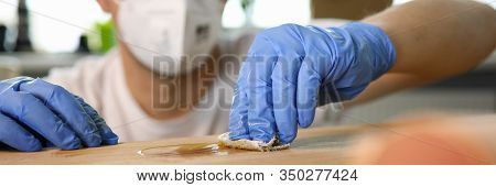 Close-up Of Male Hands Varnish Over Wooden Furniture. Man In Blue Gloves And Respirator Smearing Woo