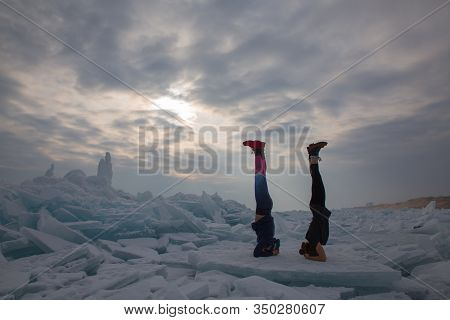 Two Girl In Winter Time Doing Yoga Elbow Stand At Ice Hummock In Frozen Lake Kapchagai Near Almaty,