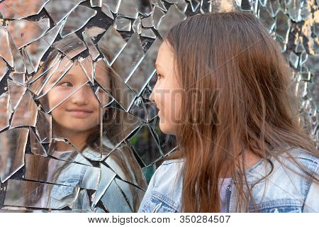 Young Girl Looks In A Broken Mirror And Smiles On A Mirror