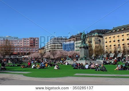 Stockholm, Sweden - April 28, 2019: Friends And Families With Children Sitting On Green Grass Near S