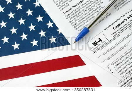 Form W-4 Employees Withholding Allowance Certificate And Blue Pen On United States Flag. Internal Re