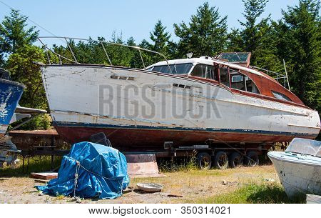 Boat Dry Docked For Repairs In Boat Yard With Smaller Boat To The Side.  This Larger Boat Is Sitting