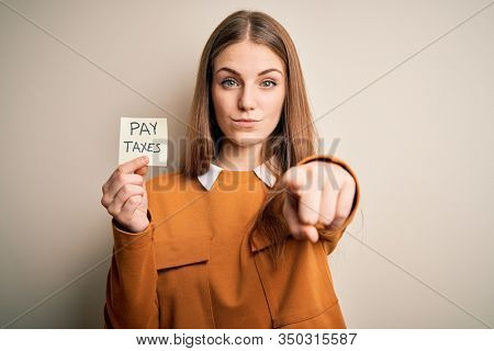 Young beautiful blonde woman holding pay taxes to goverment reminder over yellow background pointing with finger to the camera and to you, hand sign, positive and confident gesture from the front