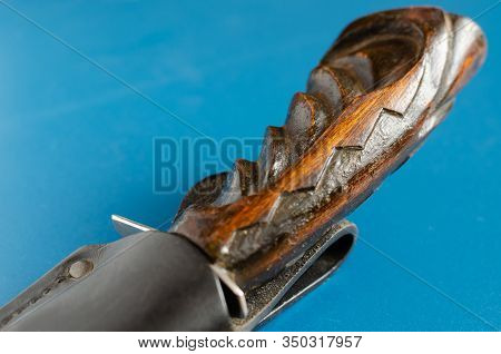 Wooden Hilt Of An Old Hunting Knife On A Blue Background. The Knife Is Hidden In Black Leather Scabb