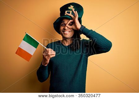 African american man wearing green hat holding irish ireland flag celebrating saint patricks day with happy face smiling doing ok sign with hand on eye looking through fingers
