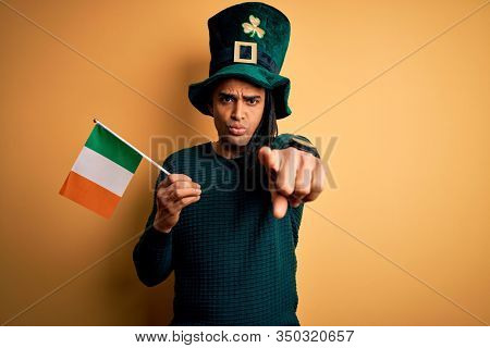 African american man wearing green hat holding irish ireland flag celebrating saint patricks day pointing with finger to the camera and to you, hand sign, positive and confident gesture from the front