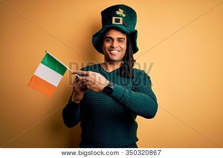African american man wearing green hat holding irish ireland flag celebrating saint patricks day very happy pointing with hand and finger