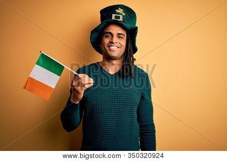 African american man wearing green hat holding irish ireland flag celebrating saint patricks day with a happy face standing and smiling with a confident smile showing teeth