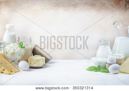Fresh Dairy Products, Milk, Cottage Cheese, Eggs, Yogurt, Sour Cream And Butter On White Table