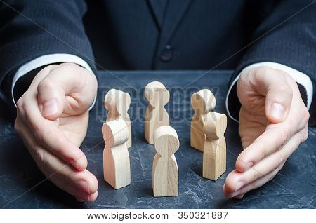 Businessman Guards A Circle Of People With His Hands. Team Insurance. Preservation Protection Of Com