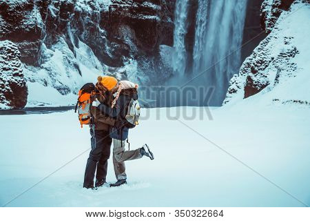 Young family travelers with pleasure spending honeymoon in Iceland, kissing near Skogafoss waterfall, happy couple in fairy tale, extreme yet romantic holiday