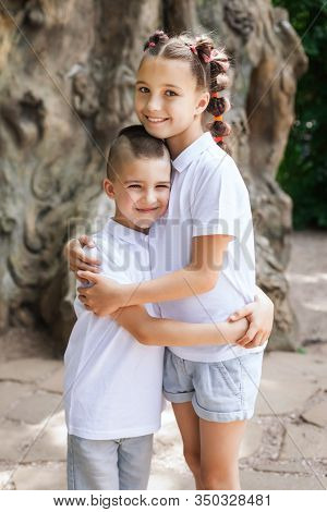 Happy Lovely Children Wearing White Shirts. Cute Girl Is Hugging Her Small Brother. Concept Of Love
