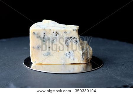 A Piece Of Cheese With Blue Mold. Cheese Dorblu On A Black Board On A Dark Background.