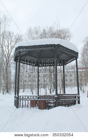 Metal Open Gazebo With Benches In Park, Covered With Snow On Cloudy Day. Concept Of Improvement And