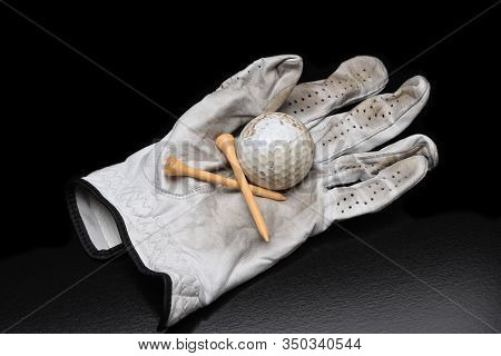 Golf Still Life. A used golf glove with tees and a dirty golf ball on black with copy space.