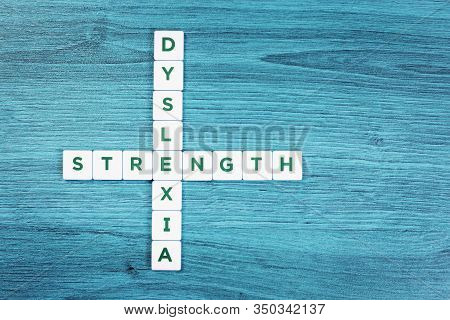 Dyslexia And Strength Word Cubes On Blue Wooden Desk Background, Reading Difficulty Awareness And Di