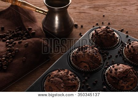 Fresh Chocolate Muffins In Muffin Tin On Wooden Surface Near Cezve With Coffee Beans On Napkin