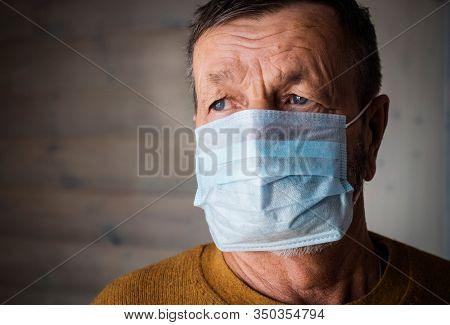 Elderly man in a medical mask. It has the flu. Coronavirus concept