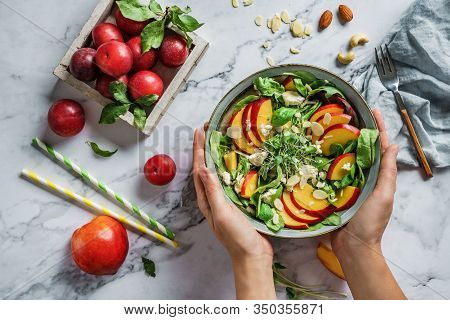 Hands Holding Fresh Summer Salad With Peach, Spinach, Micro Greens, Plums, Feta Cheese And Almonds O
