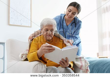 Care Worker Covering Elderly Woman With Plaid In Geriatric Hospice