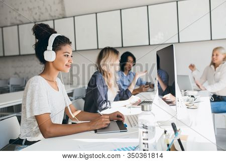 Joyful African Web-developer Working On New Project While Listening Music In White Headphones. Black