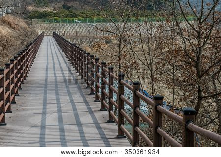 Wooden Pedestrian Bridge With Shadow Of Railing In Mountainside Park On Winter Day.