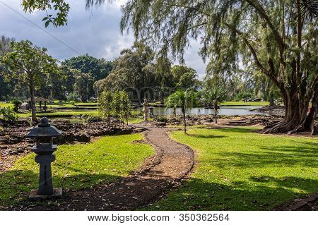 Hilo, Hawaii, Usa. - January 9, 2012: Path Winding Through Green Lawn Among Trees With Japanese Lant